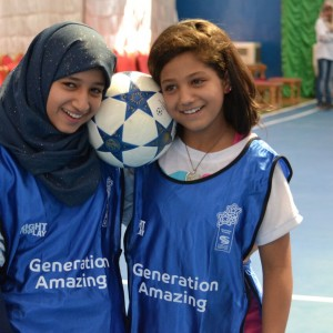 Jordan Generation Amazing pitch launch Al Baqa-a refugee camp, two girls holding ball